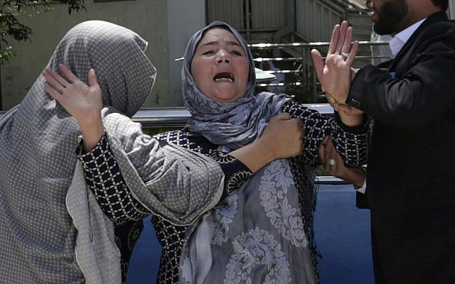 A woman cries at a hospital after she lost her son in a suicide attack on a voter registration center in Kabul, Afghanistan, Sunday, April 22, 2018. (AP Photo/Massoud Hossaini)