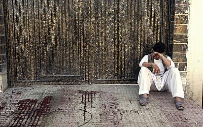 A relative of a victim cries outside a voter registration center which was attacked by a suicide bomber in Kabul, Afghanistan, Sunday, April 22, 2018. (AP Photo/ Rahmat Gul)