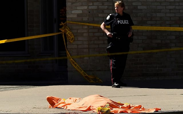 A police officer stands over a covered body in Toronto after a van mounted a sidewalk crashing into pedestrians on April 23, 2018. (Nathan Denette/The Canadian Press via AP)