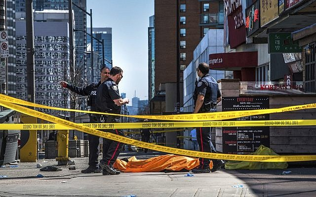 Police officers stand by a body covered on the sidewalk in Toronto after a van mounted a sidewalk crashing into a crowd of pedestrians on April 23, 2018. (Aaron Vincent Elkaim/The Canadian Press via AP)