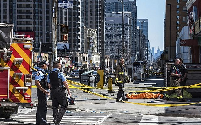 A body lies covered on the sidewalk in Toronto after a van mounted a sidewalk crashing into a number of pedestrians on April 23, 2018. (Aaron Vincent Elkaim/The Canadian Press via AP)