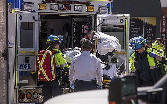 A injured person is put into the back of an ambulance in Toronto after a van mounted a sidewalk crashing into a crowd of pedestrians on April 23, 2018. (Aaron Vincent Elkaim/The Canadian Press via AP)