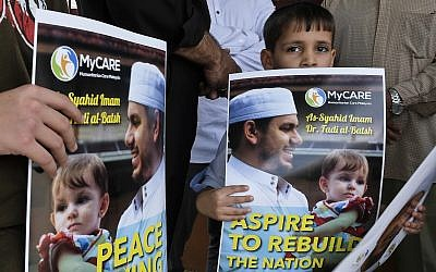 A kid holds a poster of Palestinian Fadi al-Batsh portrait at a mosque in Selayang, on the outskirt of Kuala Lumpur, Malaysia, Wednesday, April 25, 2018. (AP Photo/Sadiq Asyraf)