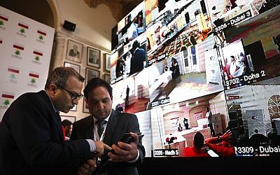 Lebanese Foreign Minister Gibran Bassil, left, talks with an assistant as they stand next to a giant screen following voting by Lebanese expatriates in six Arab countries, ahead of parliamentary elections scheduled to be held in Lebanon on May 6, at the Lebanese Foreign Ministry in Beirut, on April 27, 2018. (AP Photo/Hussein Malla)