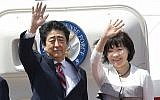 Japanese Prime Minister Shinzo Abe, left, waves with his wife Akie Abe while boarding his plane before departure for the Middle East, at Haneda international airport in Tokyo April 29, 2018. (Yukie Nishizawa/Kyodo News via AP)