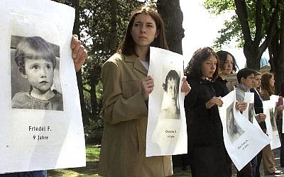 Illustrative: Young people hold pictures of children murdered at the city hospital under the Nazi euthanasia program of the physically or mentally handicapped, and their brains and other remains then used for decades for medical research, during a public service in Vienna's Central Cemetery where the last two specimens are buried, April 28, 2002. (AP Photo/Ronald Zak)