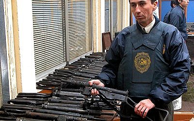 An officer stands by a large arms cache found by Chilean authorities at the commune-like Colonia Dignidad, or Dignity Colony, is displayed in Parral, Chile, some 410 kilometers (255 miles) south of Santiago, Wednesday, June, 15, 2005. (AP Photo)