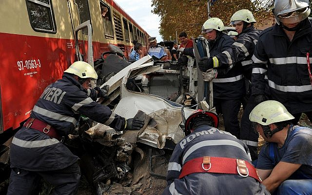 Illustrative: Romanian firefighters struggle with the wreckage of a minibus that was hit bit a train in an accident  in Scanteia, northeastern Romania, Friday, Aug. 14, 2009.  (AP Photo/Radu Aneculaesi)