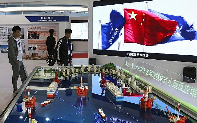 Visitors look at the models of oil tanker shaped floating nuclear reactors and oil rigs showcased at the display booth of China's state-owned China National Nuclear Corporation during the China International Exhibition on Nuclear Power Industry in Beijing, Thursday, April 27, 2017. AP Photo/Andy Wong)