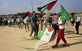 Palestinian youths fly kites and wave Palestinian and Hamas flags during a Hamas-sponsored summer scout camp, on the beach near the Israeli border fence, in Beit Lahiya, northern Gaza Strip, Wednesday, July 19, 2017. (AP Photo/Adel Hana)