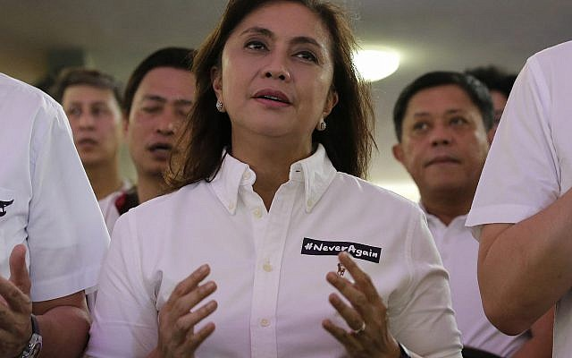 "Philippine Vice President Leni Robredo attends a mass wearing a sticker ""Never Again"" at the University of the Philippines Church of the Holy Sacrifice to commemorate the 45th anniversary of the imposition of martial law by the late Philippine dictator Ferdinand Marcos in metropolitan Manila, Philippines, September 21, 2017. (AP Photo/Aaron Favila)"