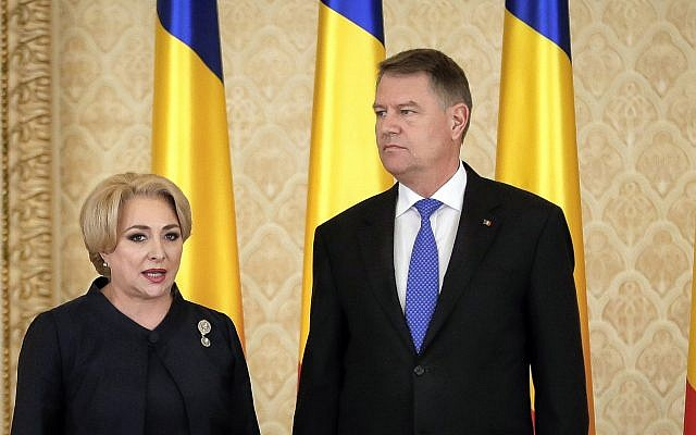 Romanian Prime Minister Viorica Dancila, left, stands next to Romania's President Klaus Iohannis after the swearing in of her cabinet, in Bucharest, Romania, Monday, January 29, 2018. (AP Photo/Vadim Ghirda)
