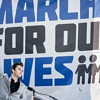 David Hogg, a survivor of the mass shooting at Marjory Stoneman Douglas High School in Parkland, Florida., raises his fist after speaking during the 'March for Our Lives' rally in support of gun control in Washington, Saturday, March 24, 2018 (AP Photo/Andrew Harnik)
