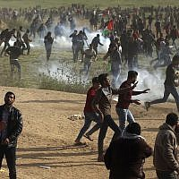 Palestinians run, as teargas canisters fired by Israeli troops land near them during a demonstration near the Gaza Strip security fence, east of Gaza City on March 30, 2018. (AP Photo/ Khalil Hamra)