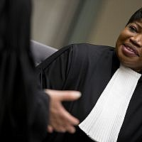 Public Prosecutor Fatou Bensouda, right, waits for alleged jihadist leader Al Hassan Ag Abdoul Aziz Ag Mohamed Ag Mahmoud to enter the court room for his initial appearance on charges of war crimes and crimes against humanity at the International Criminal Court in The Hague, Netherlands, Wednesday, April 4, 2018. After his capture in Mali, the court in The Hague said that Al Hassan allegedly committed the crimes in Timbuktu while the town was under the control of extremists between April 2012 and January 2013. (AP Photo/Peter Dejong, Pool)