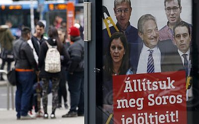 "People stand on a street by a billboard from Prime Minister Viktor Orban's Fidesz party which reads, ""Let's stop Soros' candidates!"" showing American financier George Soros, center, and, from left, Bernadett Szel of the Politics Can Be Different party, Ferenc Gyurcsany from the Democratic Coalition, Gergely Karacsony of the Dialogue party and Gabor Vona of the Jobbik party, in Budapest, Hungary,  April 7, 2018. (AP Photo/Darko Vojinovic)"