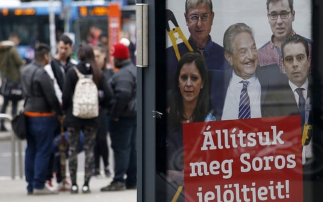 People stand on a street by a billboard from Prime Minister Viktor Orban's Fidesz party which reads, 'Let's stop Soros' candidates!' showing American financier George Soros, center, and, from left, Bernadett Szel of the Politics Can Be Different party, Ferenc Gyurcsany from the Democratic Coalition, Gergely Karacsony of the Dialogue party and Gabor Vona of the Jobbik party, in Budapest, Hungary,  April 7, 2018. (AP Photo/Darko Vojinovic)