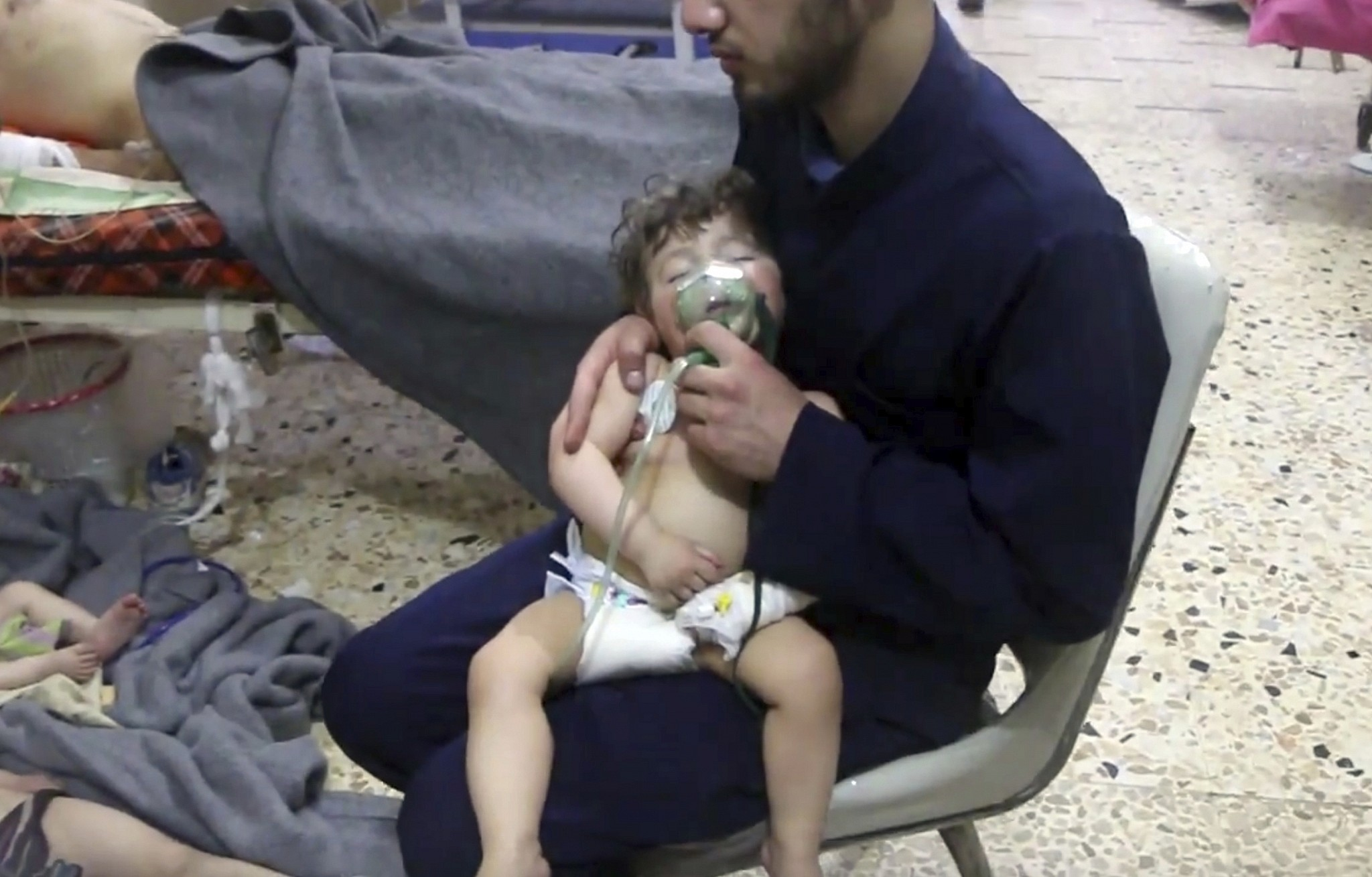 This image shows a medical worker giving toddlers oxygen through respirators following an alleged poison gas attack in the opposition-held town of Douma in eastern Ghouta near Damascus Syria Sunday