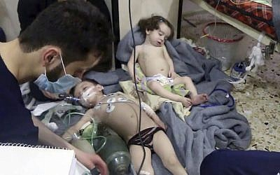 Medical workers treating toddlers following an alleged poison gas attack in the opposition-held town of Douma, in Eastern Ghouta, near Damascus, Syria, April. 8, 2018 (Syrian Civil Defense White Helmets via AP)