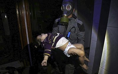 This image released early Sunday, April 8, 2018 by the Syrian Civil Defense White Helmets, shows a rescue worker carrying a child following an alleged chemical weapons attack in the rebel-held town of Douma, near Damascus, Syria. (Syrian Civil Defense White Helmets via AP)