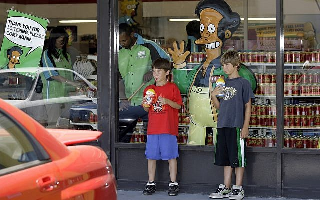 "Children pause next to a poster with ""The Simpsons"" character Apu Nahasapeemapetilon Jr. outside a 7-Eleven Kwik-E-Mart in Burbank, Calif. (AP Photo/Damian Dovarganes, File)"