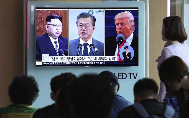 People watch a TV screen showing file footage of US President Donald Trump, right, South Korean President Moon Jae-in and North Korean leader Kim Jong Un, left, during a news program at the Seoul Railway Station in Seoul, South Korea, April 18, 2018 (AP Photo/Ahn Young-joon, File)