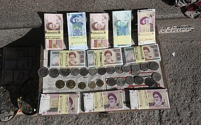Illustrative photo of Iranian banknotes and foreign coins displayed by a vendor on a side walk of the Ferdowsi Street in Tehran, Iran, January 23, 2013. (Vahid Salemi/AP)