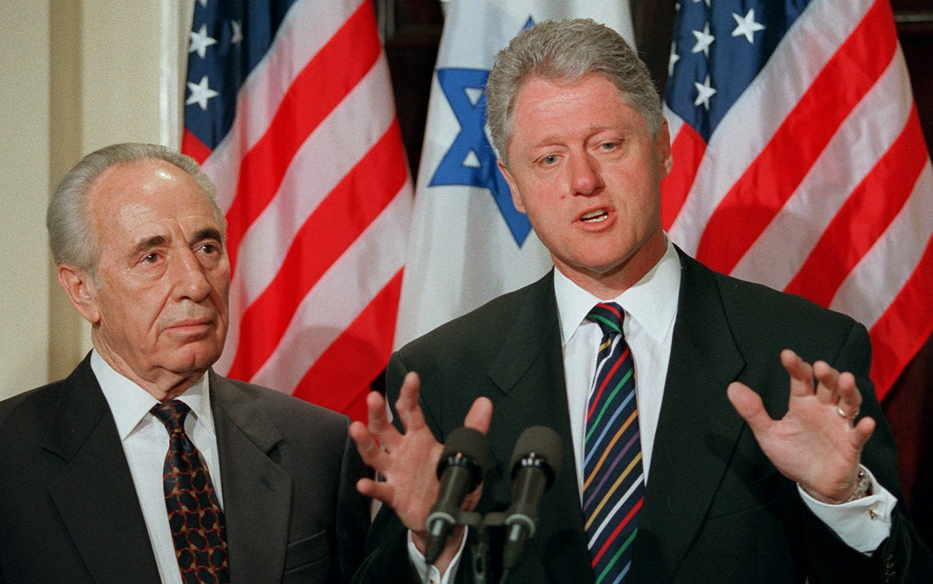 Prime minister Shimon Peres looks on as President Bill Clinton answers a  reporters question at the