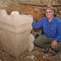 Prof. Aren Maeir next to a stone altar found in a temple at the site of Tell es-Safi/Gath. (Richard Wiskin)