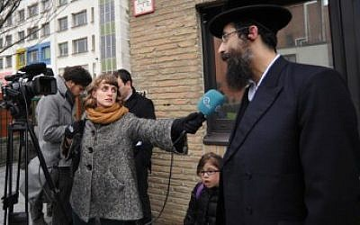 Aron Berger (r) being interviewed earlier this year by a Belgian journalist outside his daughter's state-funded elementary school in Antwerp in August 2013. (Cnaan Liphshiz/JTA)