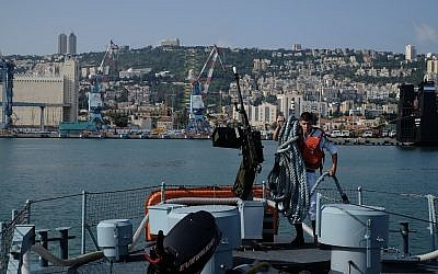 A crewmember of a Dvora patrol boat gets the ship ready in the Haifa port for the Israeli Navy's flotilla in honor of Israel's 70th Independence Day on April 19, 2018. (Judah Ari Gross/Times of Israel)