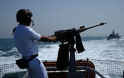 A crewmember of a Dvora patrol boat poses with the ship's machine gun during the Israeli Navy's flotilla in honor of Israel's 70th Independence Day on April 19, 2018. (Judah Ari Gross/Times of Israel)