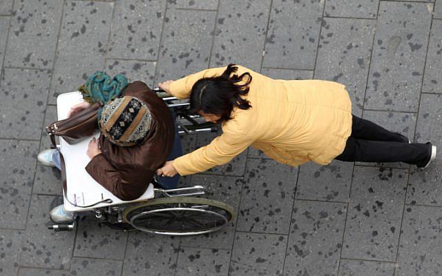 Illustrative: A caregiver walks with an elderly man in a wheelchair (Nati Shohat/Flash90)