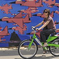 Illustrative: A young Israeli woman rides her bicycle past graffiti in Tel Aviv on May 14, 2012. (Serge Attal/Flash90)