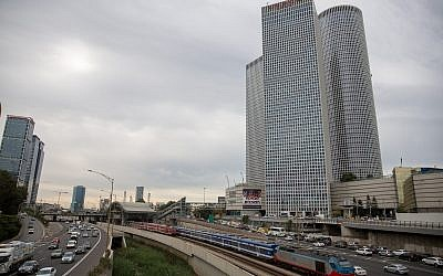 Train tracks and the Ayalon highway in central Tel Aviv, with the Azrieli Towers as a backdrop, December 18, 2017. (Miriam Alster/Flash90)