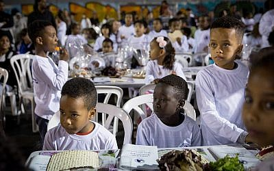 Students from Bialik School, in South Tel Aviv, many of them children of African asylum-seekers, attend a pre-Passover seder in the schoolyard on March 20, 2018. (Miriam Alster/FLASH90)
