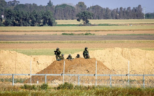 Israeli soldiers watch Palestinian protesters following a demonstration near the border with Israel, east of Khan Yunis, in the southern Gaza Strip on March 31, 2018. (Abed Rahim Khatib/ Flash90)