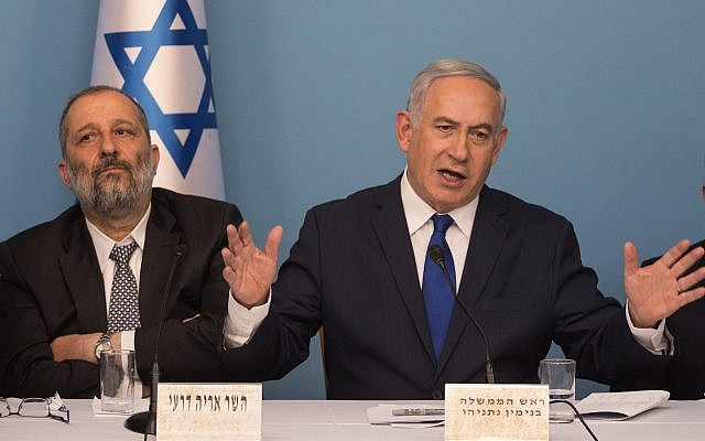 Prime Minister Benjamin Netanyahu (right) and Interior Minister Aryeh Deri announce a new refugee deal with the UN, hours before suspending it, April 2, 2018 (Hadas Parush/Flash90)