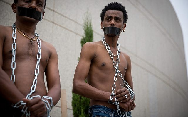 African asylum seekers set up a mock slave auction as part of a protest outside the Ministry of Defense in Tel Aviv, against their deportation, on April 3, 2018. (Miriam Alster/ Flash90)