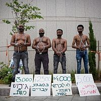 African asylum seekers set up a mock slave auction as part of a protest against their deportation outside the Ministry of Defense in Tel Aviv,, on  April 3, 2018. (Miriam Alster/Flash90)