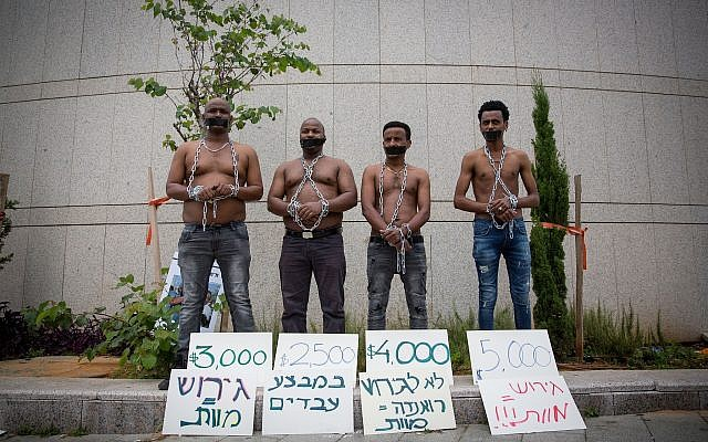 African asylum seekers set up a mock slave auction as part of a protest against their deportation outside the Ministry of Defense in Tel Aviv, on  April 3, 2018. (Miriam Alster/Flash90)