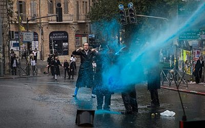 Ultra-Orthodox Jewish men clash with police during a protest against the autopsy of the baby that drowned to death yesterday in Ashdod, at Kikar HaShabat, in Jerusalem, on April 3, 2018. (Noam Revkin Fenton/Flash90)