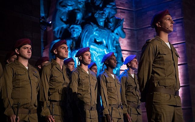 Israeli soldiers stand below a monument at a ceremony at the Yad Vashem Holocaust Memorial Museum in Jerusalem, as Israel marks Holocaust Remembrance Day, April 11, 2018 (Yonatan Sindel/Flash90)