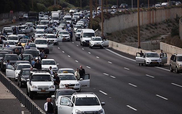People stand still on the Ayalon highway in Tel Aviv as a two-minute siren is sounded across Israel to mark Holocaust Remembrance Day on April 12, 2018. (Miriam Alster/Flash90)