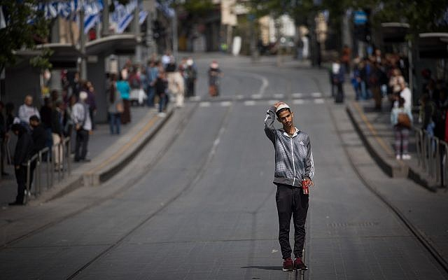 People stand still on Jaffa road, central Jerusalem, as a two-minute siren is sounded across Israel to mark Holocaust Remembrance Day on April 12, 2018. (Yonatan Sindel/Flash90)