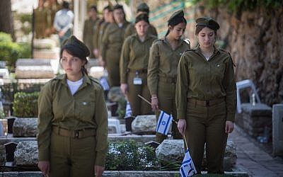 Soldiers place Israeli flags on the graves of fallen soldiers in Mount Herzl Military Cemetery in Jerusalem on April 16, 2018 ahead of Memorial Day for Israel's Fallen Soldiers. (Hadas Parush/Flash90)