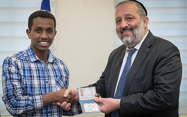 Sintayehu Shafrao from Ethiopia, who is competing in the annual International Bible Quiz in Israel, receives a National ID from Israel Minister of Interior Affairs Aryeh Deri during a ceremony at the Interior ministry office in Jerusalem on April 16, 2018. (Yonatan Sindel/Flash9)