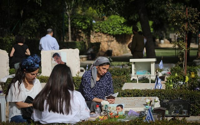 Illustrative: Bereaved Israelis mourn next to graves of fallen soldiers at the Mount Herzl military cemetery in Jerusalem, during Israeli Memorial Day, April 18, 2018. (Miriam Alster/Flash90)