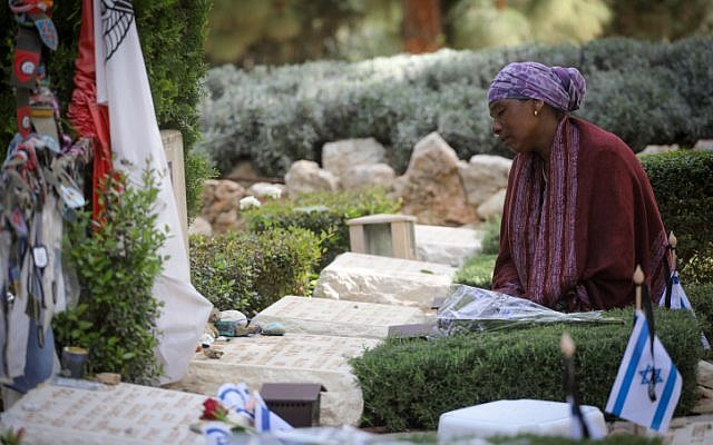 Bereaved Israelis mourn next to graves of fallen soldiers at the Mt Herzl military cemetery in Jerusalem, during Israeli Memorial Day, commemorating the deaths of Israeli soldiers killed in wars since 1860, and Israeli victims of terror. April 18, 2018. (Miriam Alster/Flash90)