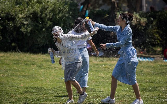 Israelis play with foam spray during Israel's 70th Independence Day celebrations in Sacher Park in Jerusalem, April 19, 2018. (Yonatan Sindel/Flash90)